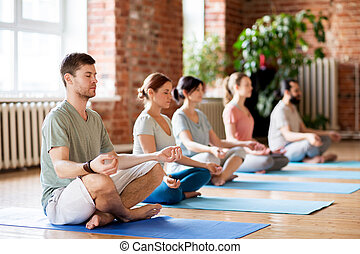 group of people making yoga exercises at studio - fitness,...