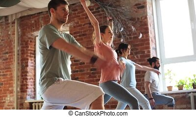 group of people making yoga exercises in gym