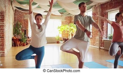 group of people making yoga exercises in gym - fitness,...