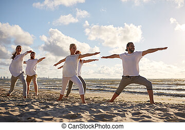 group of people making yoga exercises on beach - fitness,...
