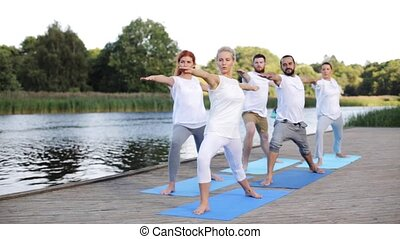 fitness, sport, and healthy lifestyle concept - group of people making yoga in warrior pose on river or lake berth