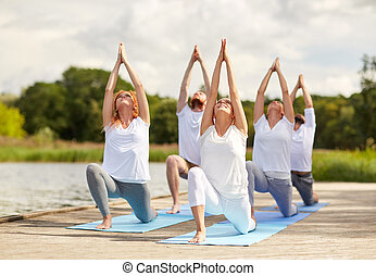 group of people making yoga exercises outdoors - fitness, ...