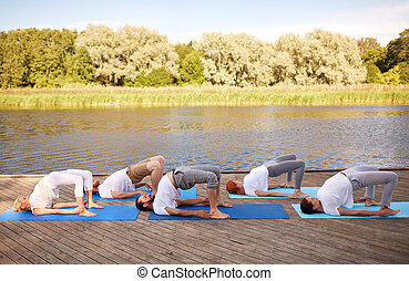 fitness, sport, yoga and healthy lifestyle concept - group of people making bridge pose on river or lake berth