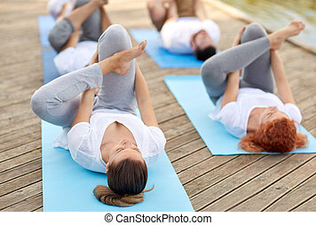 group of people making yoga exercises outdoors - fitness,...
