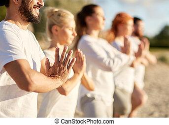 group of people making yoga or meditating on beach - yoga,...
