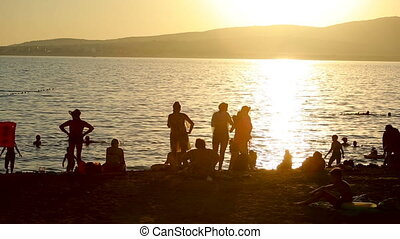 group of people on a background of the sea. silhouettes at sunset. summer beach