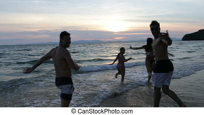 Group Of People On Beach At Sunset Running In Sea Making Splashes Cheerful Friends On Vacation