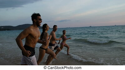 Group Of People On Beach At Sunset Running In Sea Making Splashes Mix Race Cheerful Friends On Vacation