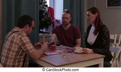 Group of people play a board game in a cafe