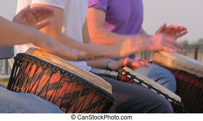 Group of people playing ethnic drums on street