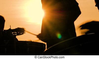 Unrecognizable group of people silhouette playing ethnic percussion drum musical instruments on street at sunset - close up shot. Street music and urban culture concept