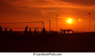 Group of people playing volleyball on a public beach at sunset