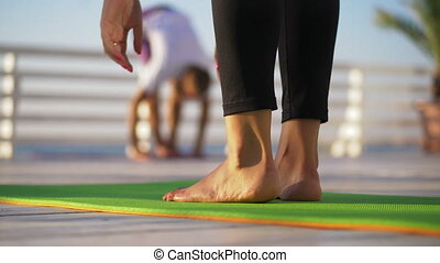 Group of people practicing yoga on the beach in 4k. Focus on legs which standing on yoga mat.