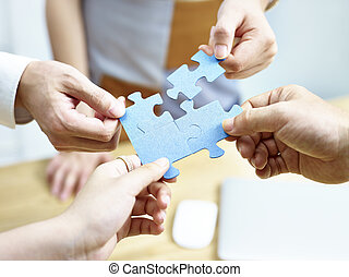 group of people putting jigsaw pieces together - group of...