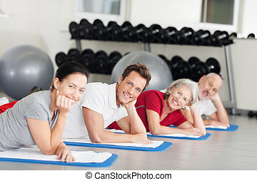 Group of people relaxing while training at the gym