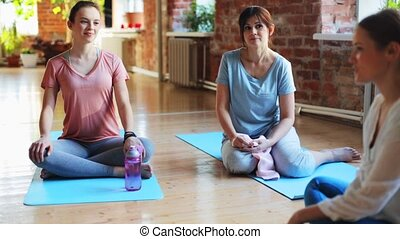 group of people resting on yoga mats in gym