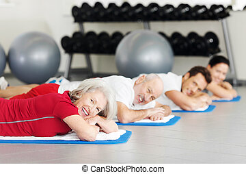 Group of people resting while working out at a gym
