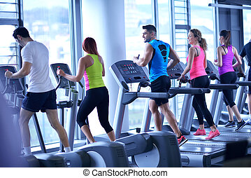 Group of people running on treadmills - group of young ...