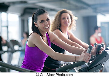 Group of people running on treadmills