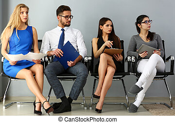 Group of people sit on casting chairs row