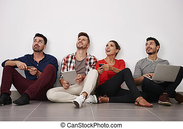 Group of people sitting next to the wall