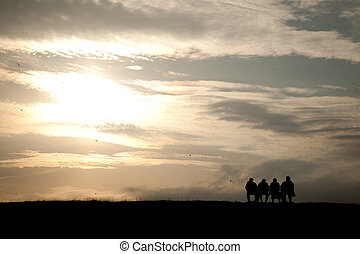 group of people sitting on a bench in the sunset on a dike...
