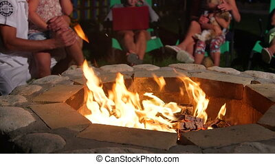 Group of people sitting on patio loungers around stone fire pit in back yard