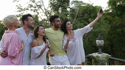 Group Of People Taking Selfie Photo On Terrace Over Sunset, Friends Posing For Self Portrait Outdoors