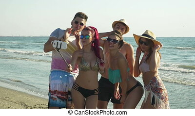 Group of people taking selfies and having a video call on the shore of a beautiful beach
