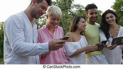 Group Of People Talking Holding Cell Smart Phones On Terrace Over Sunset Landscape, Young People Communicating Messaging Online Outdoors