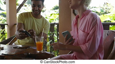 Group Of People Talking Using Cell Smart Phones Sit Together At Table On Terrace Surfing Internet Outdoors, Friends Chatting Online