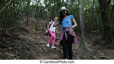 Group Of People Trekking On Forest Path Climbing Downhill,...
