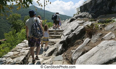 Group of people walking along tourist path in mountains