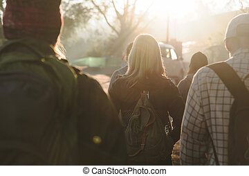 Group of people walking by the road in beautiful sunlight. Back view