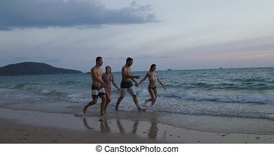 Group Of People Walking On Beach At Sunset, Two Mix Race Couple Communication During Summer Vacation