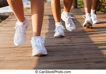 group of people walking on beach for exercising in the morning