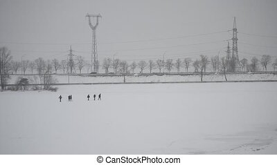 Group of people walking on ice covered with snow towards dike