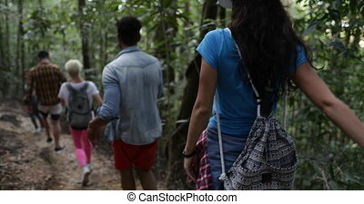 Group Of People with Backpacks Walking Through Woods,...