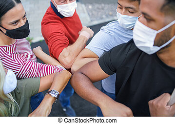 Top view of group of people with face masks elbow bumping, coronavirus, covid-19 concept.