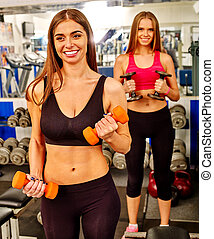 Group of people  working with dumbbells  at gym.