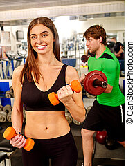 Group of people working with dumbbells .