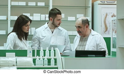 Group of pharmacist have an emotional discussion with documents in pharmacy