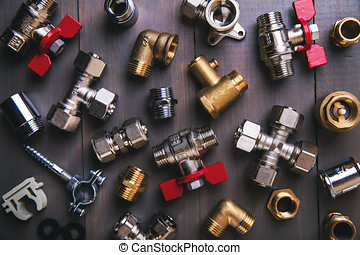 group of plumbing fittings and equipment on wooden background