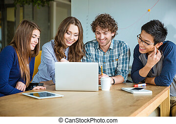 Group of positive cheerful students doing homework together in classroom
