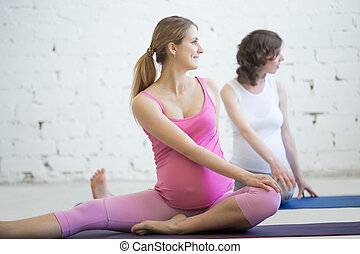 Group of pregnant women doing prenatal yoga. Spinal twist in Janu Sirsasana pose