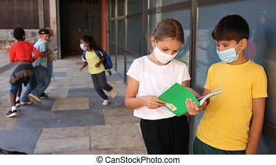 Group of preteen children in face masks resting outdoors in schoolyard during break in lessons. Back school concept during pandemic. High quality FullHD footage