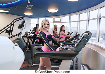 Group of pretty girls training in fitness centre