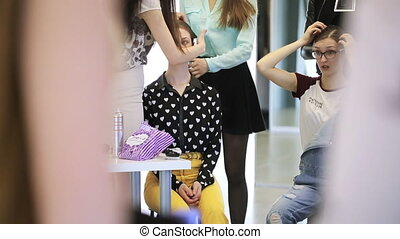 Group of pretty women is busy with smartening up in dressing room.