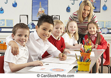 Group Of Primary Schoolchildren And Teacher Working At Desks...