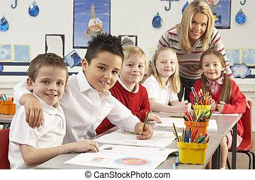 Group Of Primary Schoolchildren And Teacher Working At Desks...